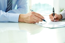 Two people signing estate planning documents in a business setting.